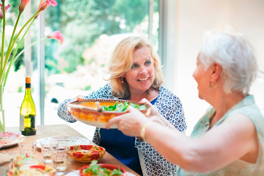 Two women at a dining table passing salad