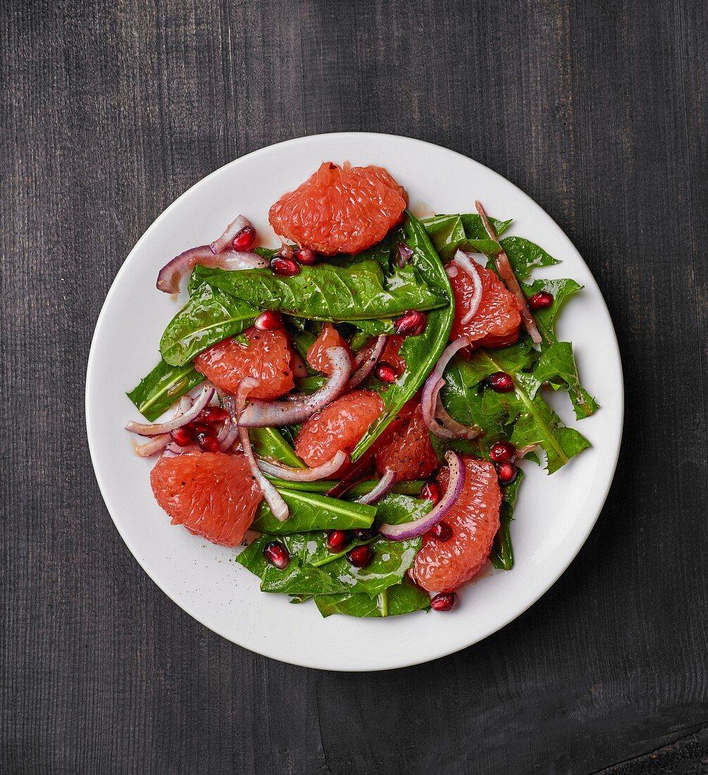 Löwenzahnsalat mit Grapefruit, roten Zwiebeln und Granatapfelkernen