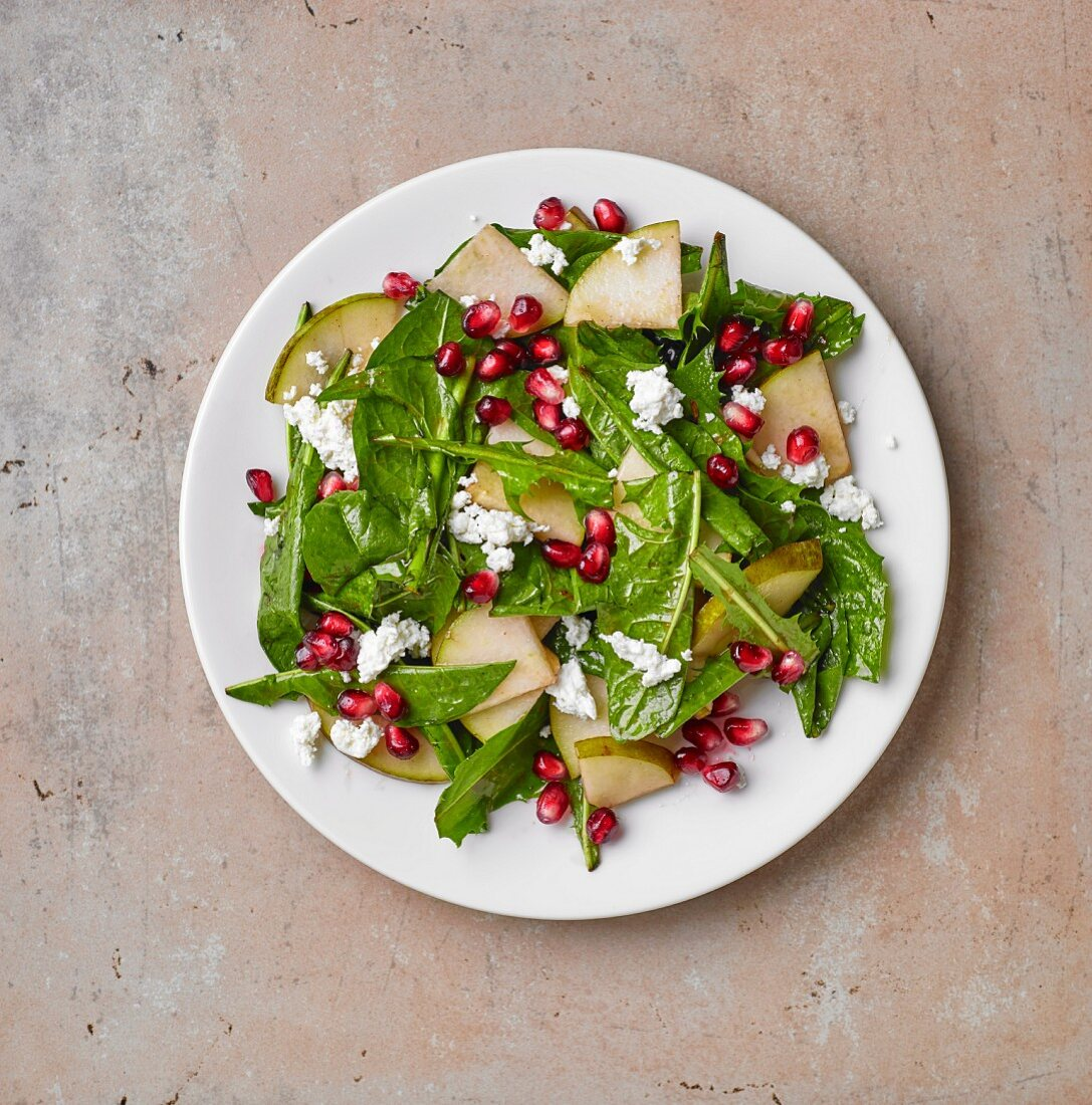 Dandelion salad with pear, pomegranate seeds and cream cheese