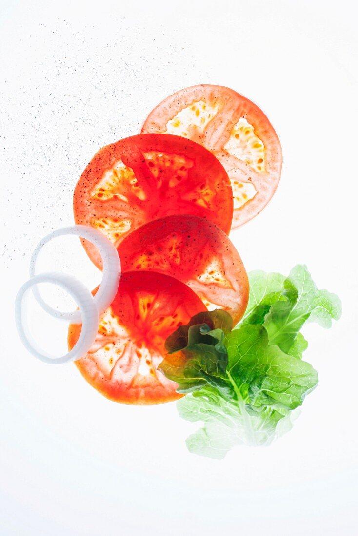 Tomatenscheiben, Zwiebelringe und Salatblatt
