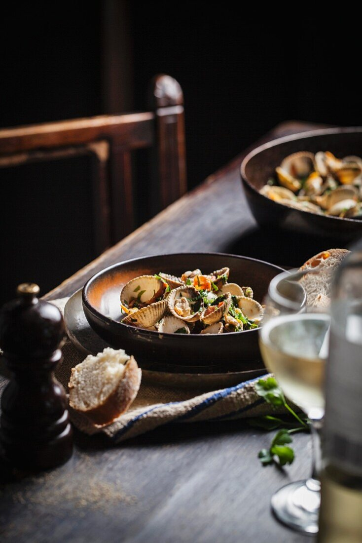 Clams in a herb sauce with white bread and wine