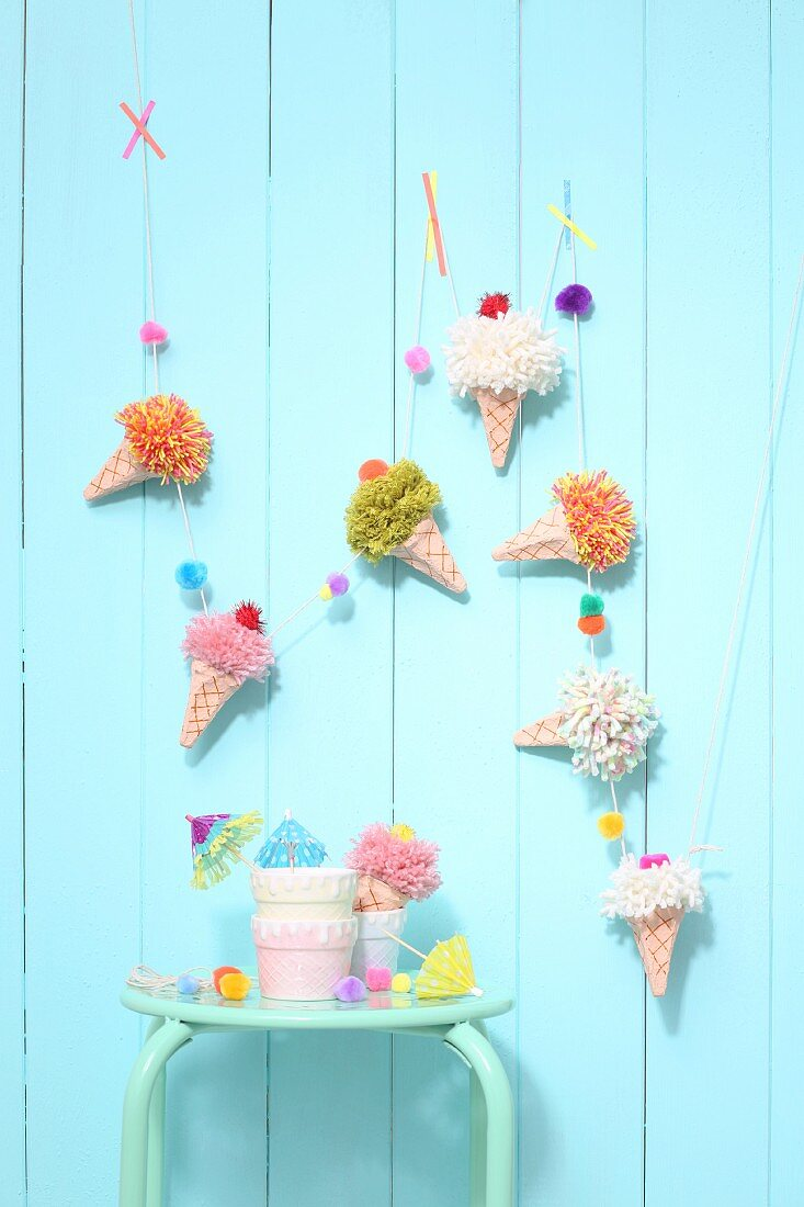 Garland made from egg cartons and wool remnants hung on pale blue wall