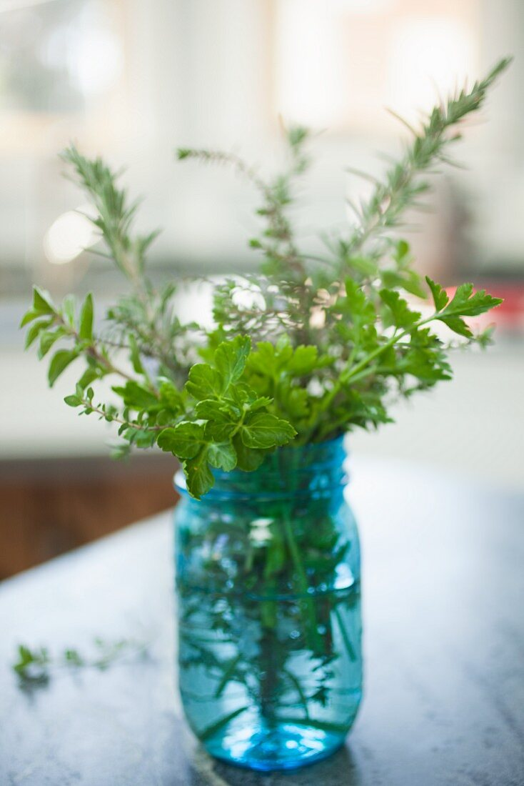 A bouquet of herbs in a blue glass