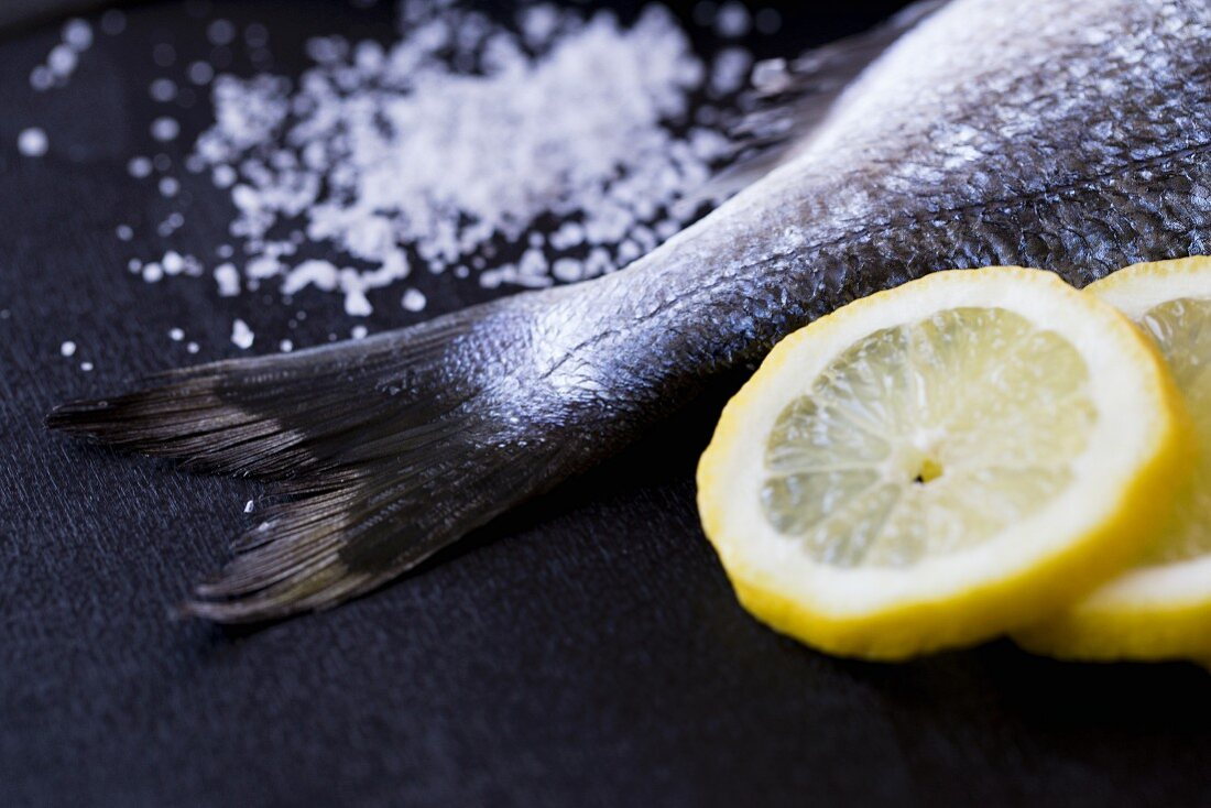 A seabream tail with salt and lemon slices (ingredients for seabream in a salt crust)