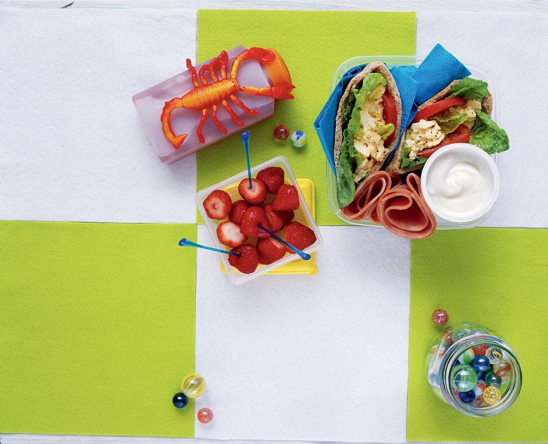 Pita bread with egg salad, ham rolls and strawberries with vanilla yoghurt for a school break
