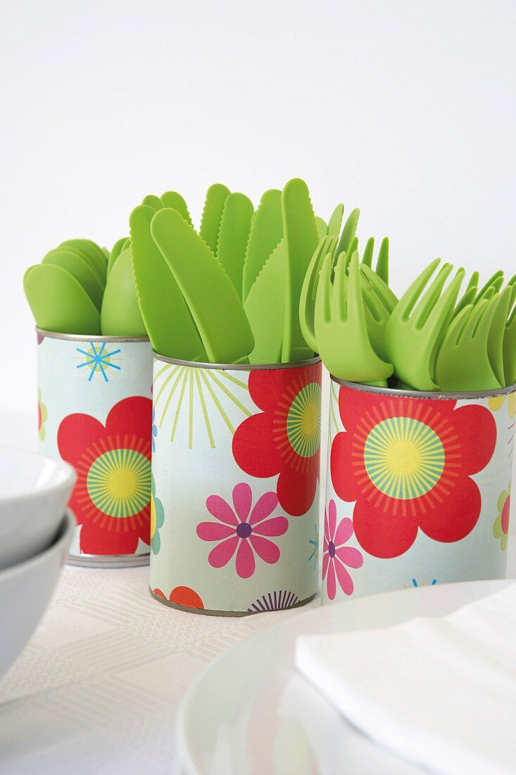 Tin cans covered with floral paper used as cutlery holders