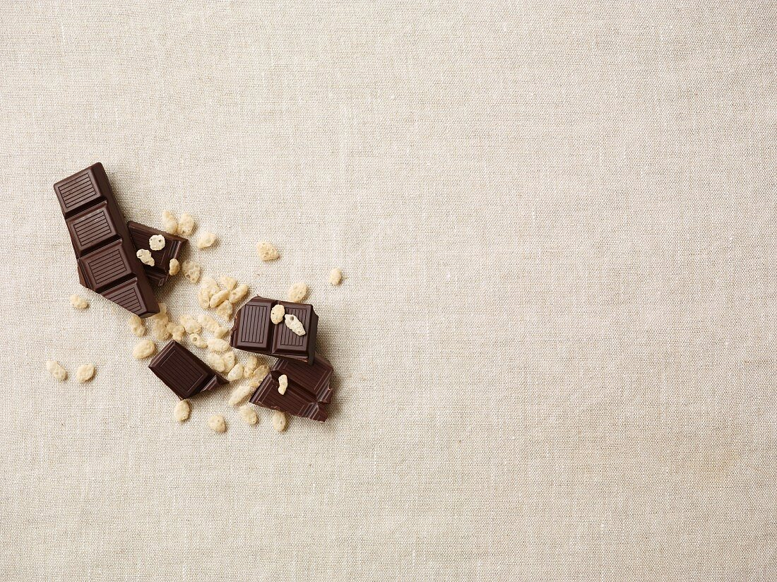 Dark chocolate and crispy cereals on a white tablecloth