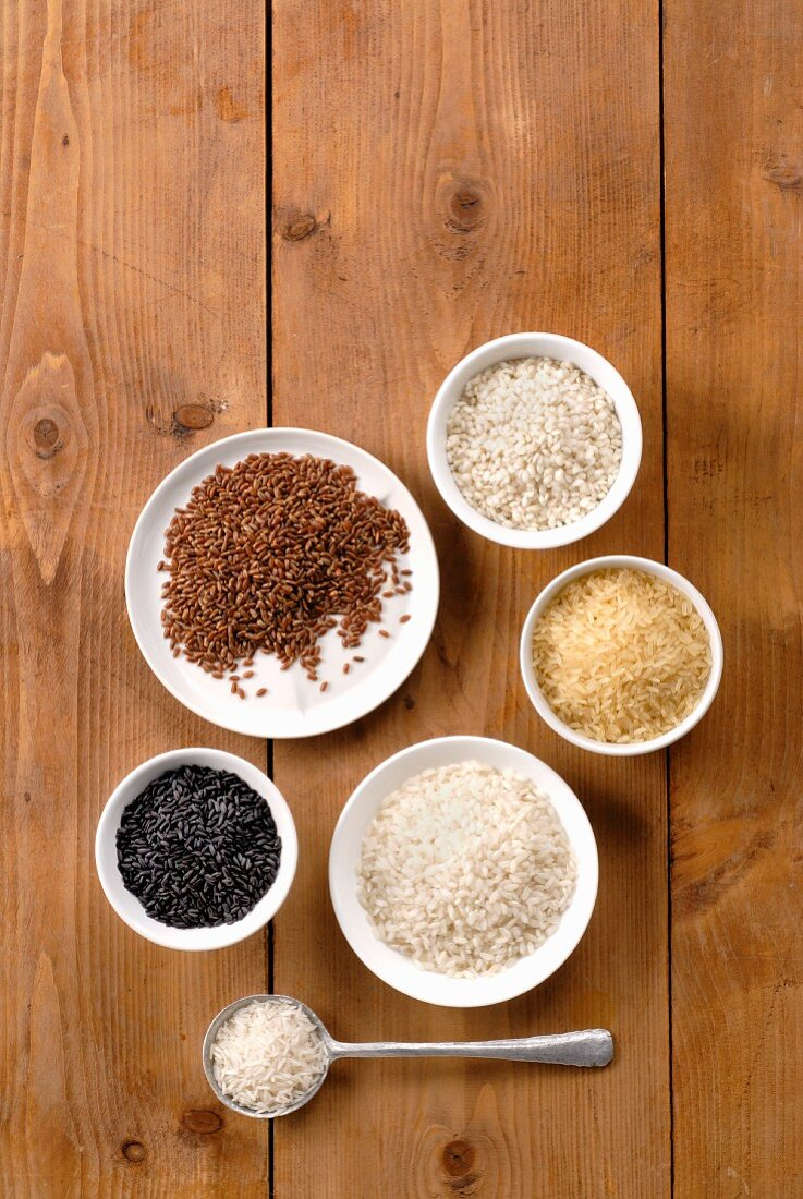 Various types of rice in bowls on wooden surface