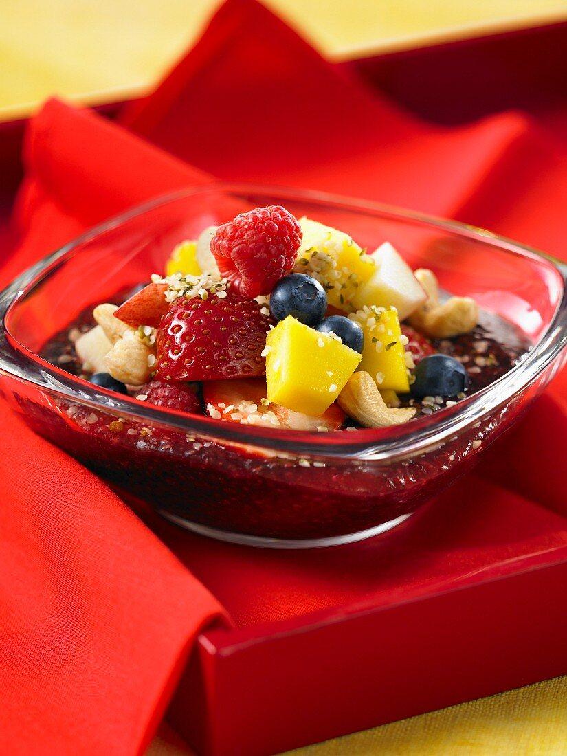 Fruit salad with strawberries, raspberries, blueberries, mango, cashew nuts and acai juice