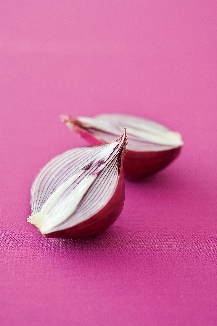 A halved red onion on a pink surface