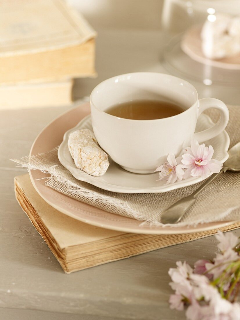 A cup of tea with blossom and a biscuit