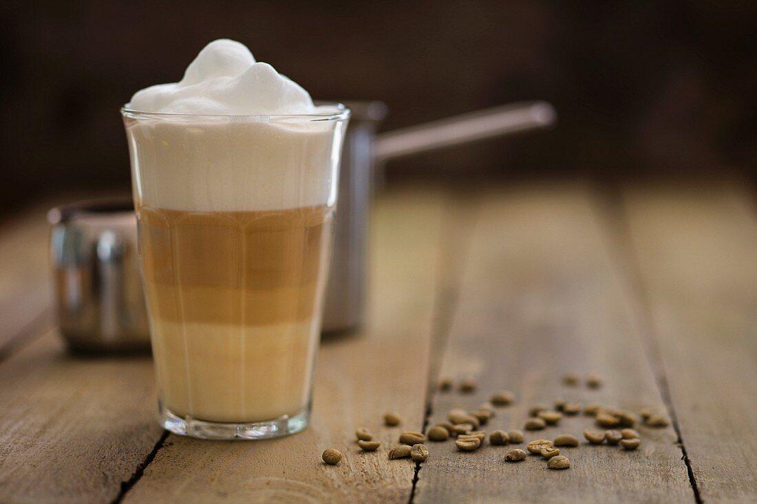 Latte macchiato mit grünen Kaffeebohnen