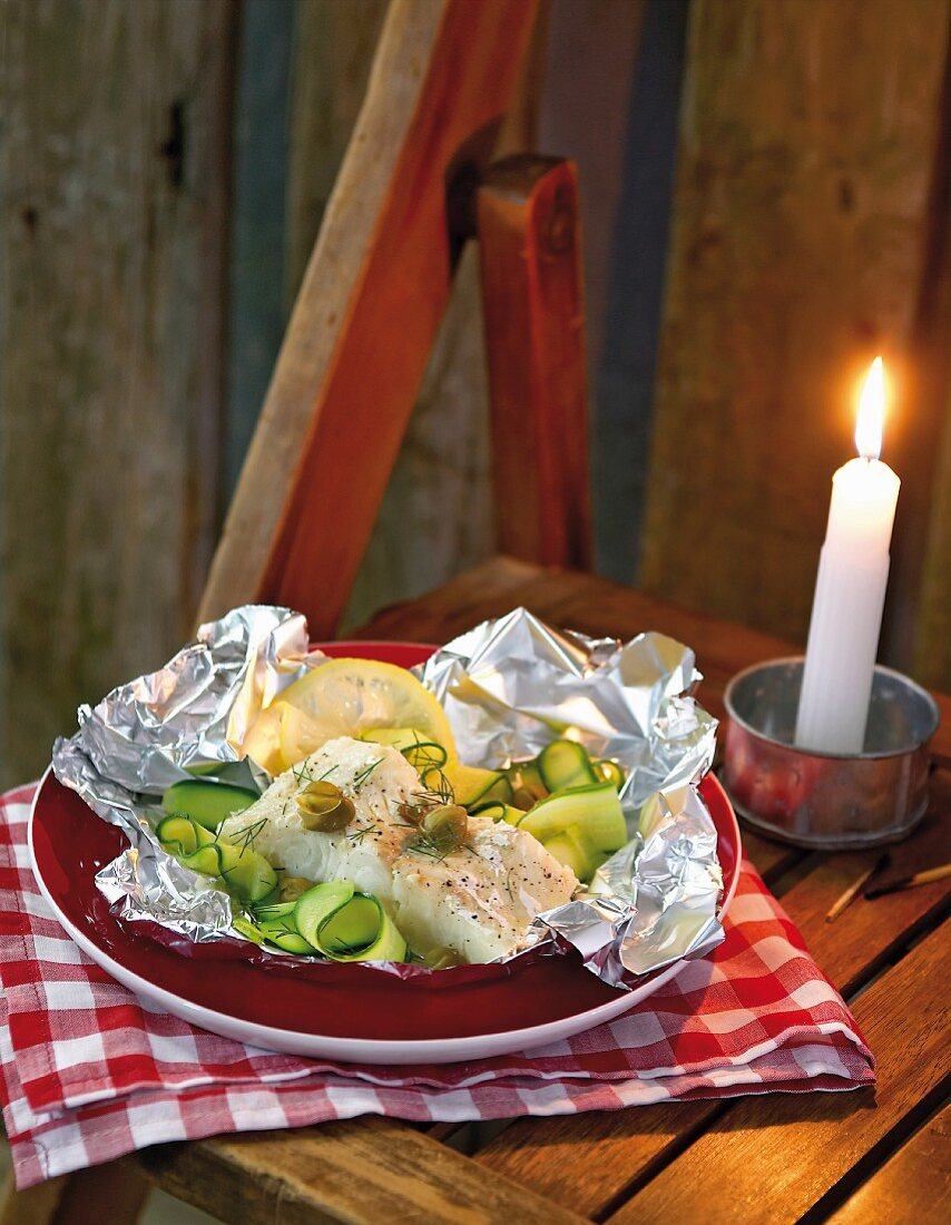 Hake with courgettes, capers and lemon baked in paper