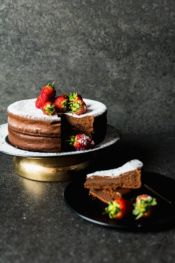 Chocolate cake with icing sugar and strawberries, sliced