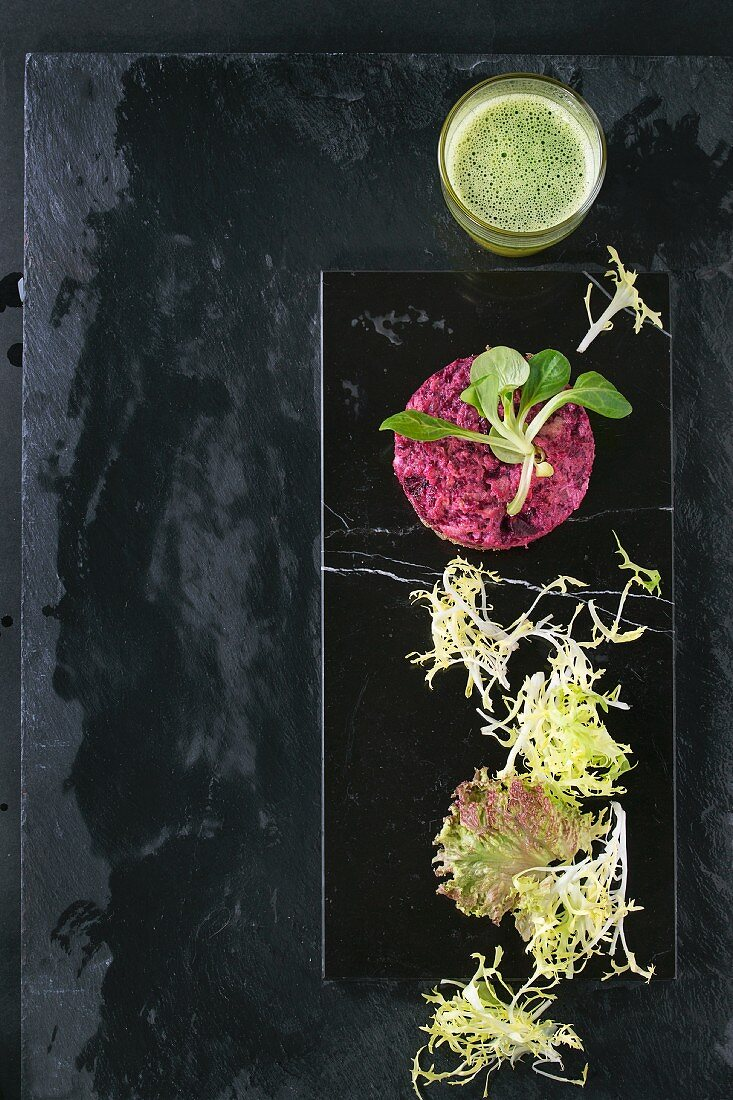 Beetroot scrambled eggs with a green salad served with a green smoothie