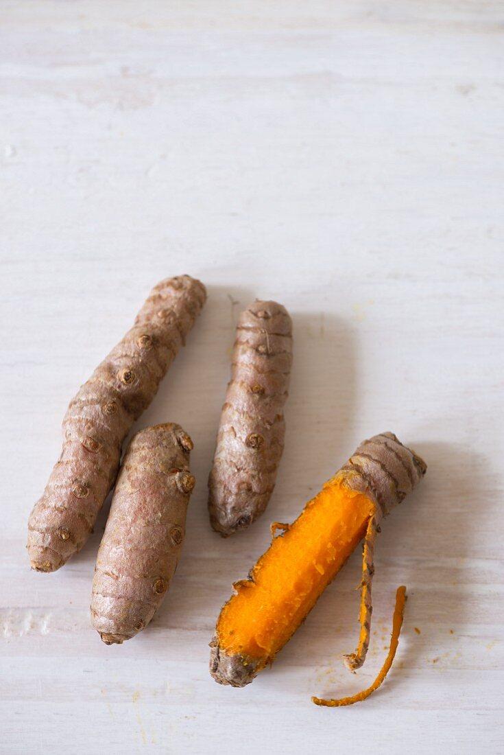 Fresh turmeric roots, peeled and unpeeled