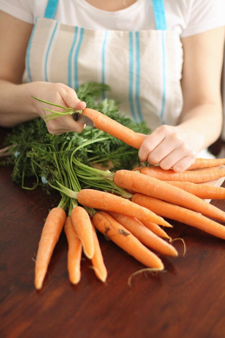 A woman removing the leaves from a bundle of carrots