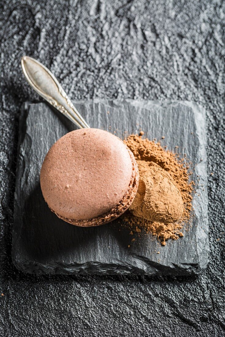 Chocolate macaroons with cocoa powder on a black stone