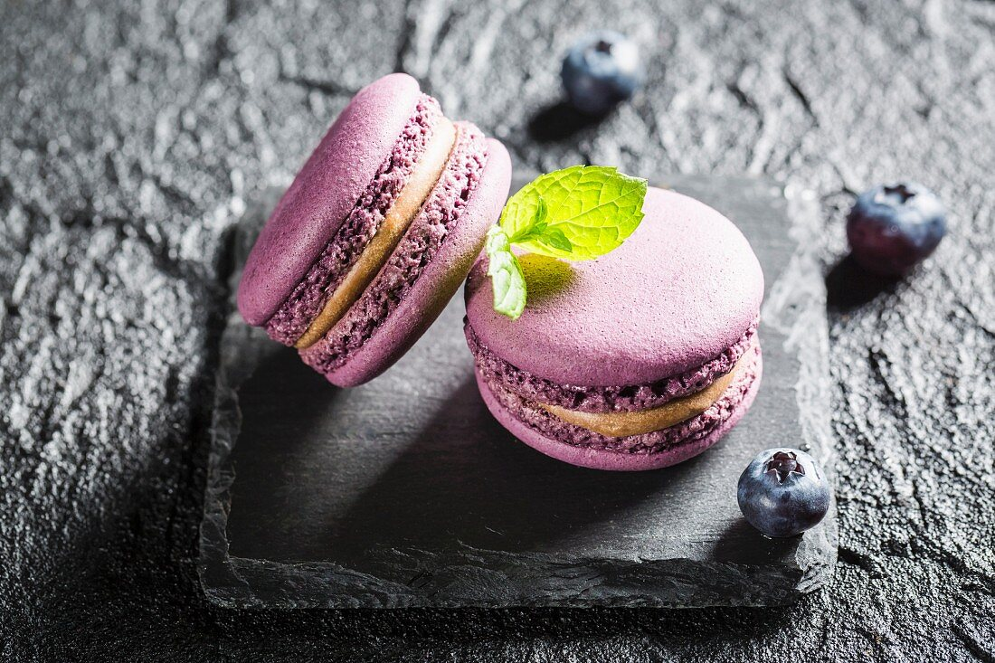 Blueberry macaroons on a black stone