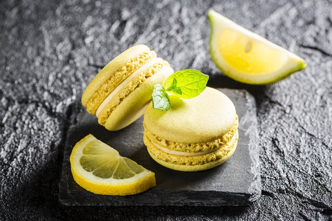 Zitronen-Macarons auf schwarzem Stein