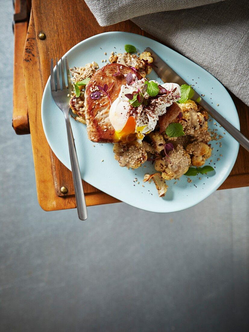 Spicy fried cauliflower with tahini, sesame seeds, tuna, and a poached egg