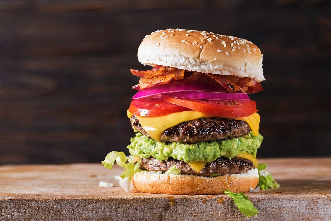 A double bacon cheeseburger with guacamole, tomatoes and onions