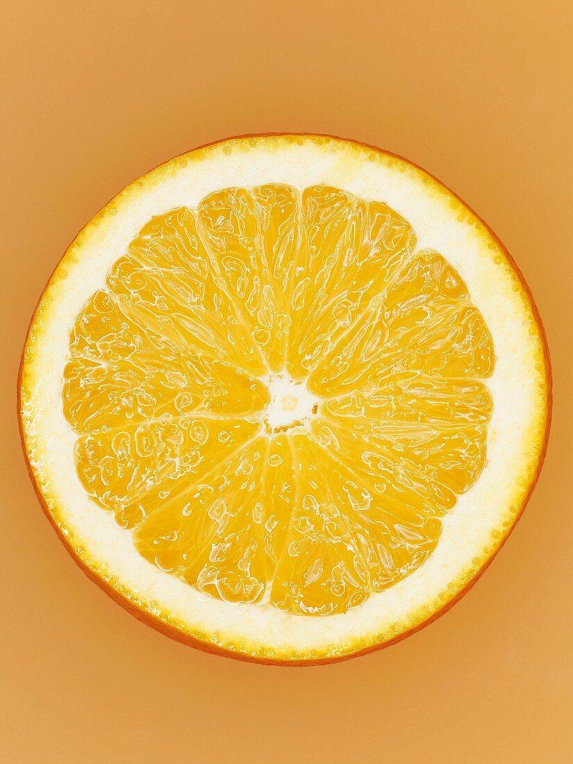 A slice of orange on orange surface, close-up