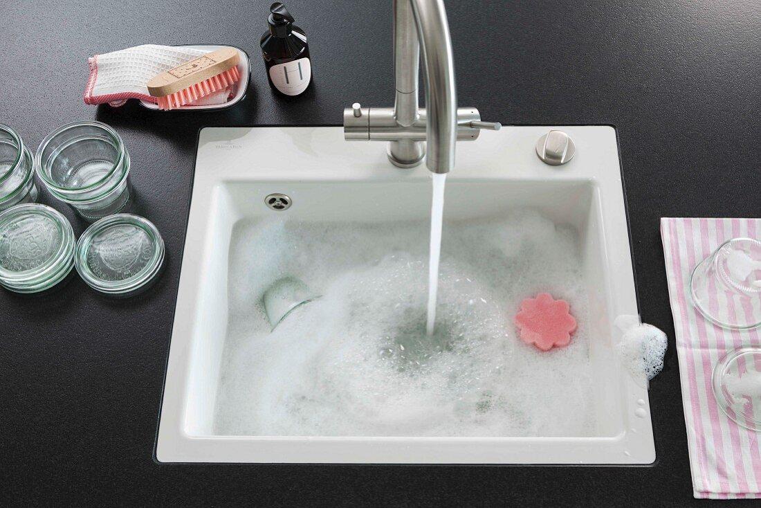 In Kücheninsel eingebautes Spülbecken mit fliessendem Wasser
