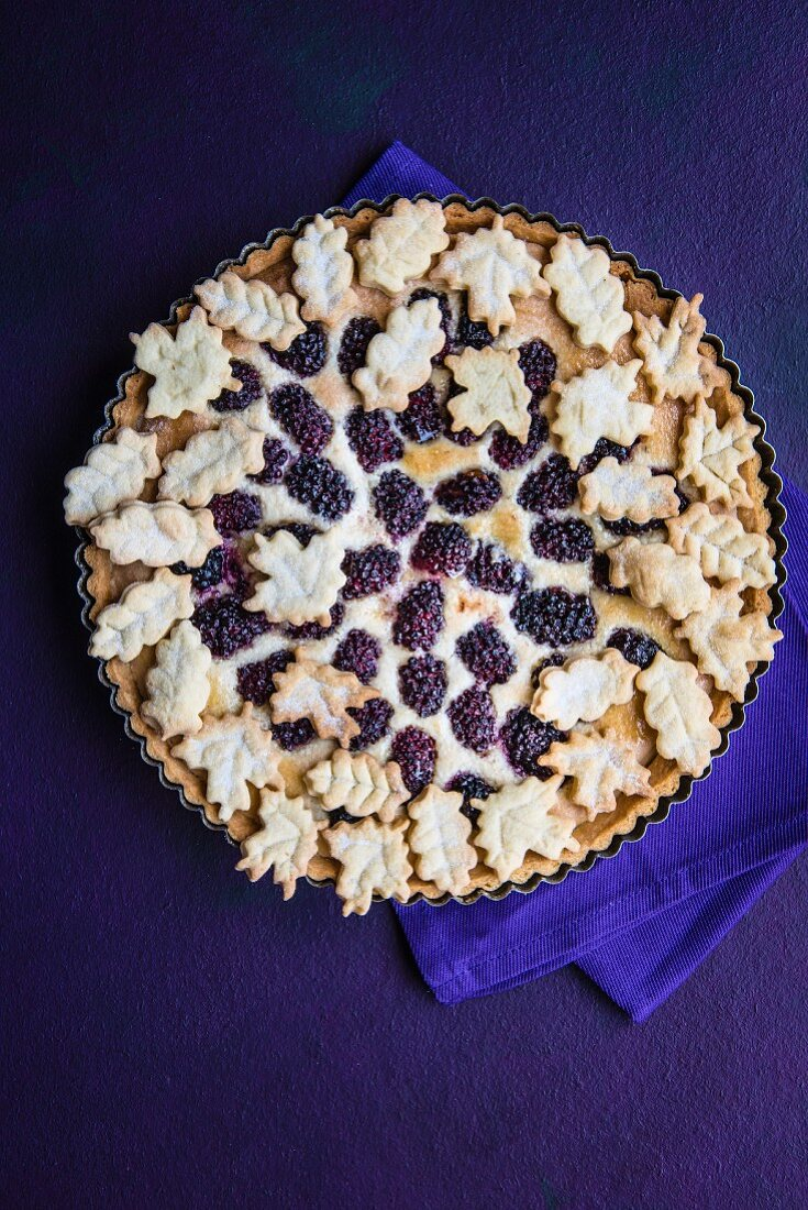 A whole blackberry and almond tart decorated with pastry leaves (seen from above)