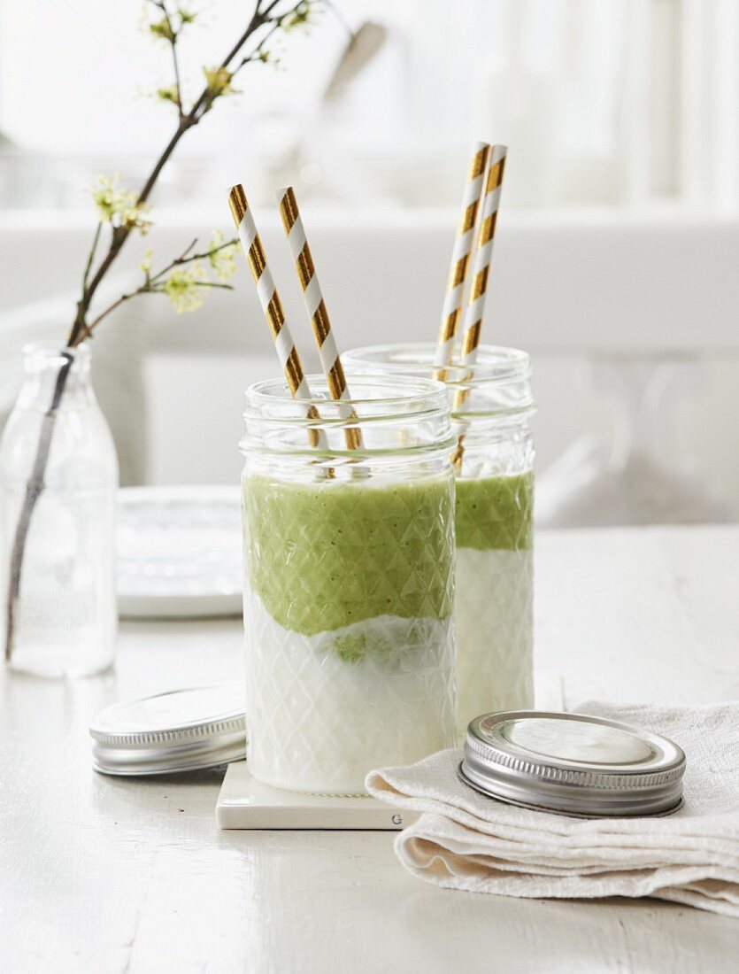 A green smoothie with avocado and matcha poured over yoghurt in a glass