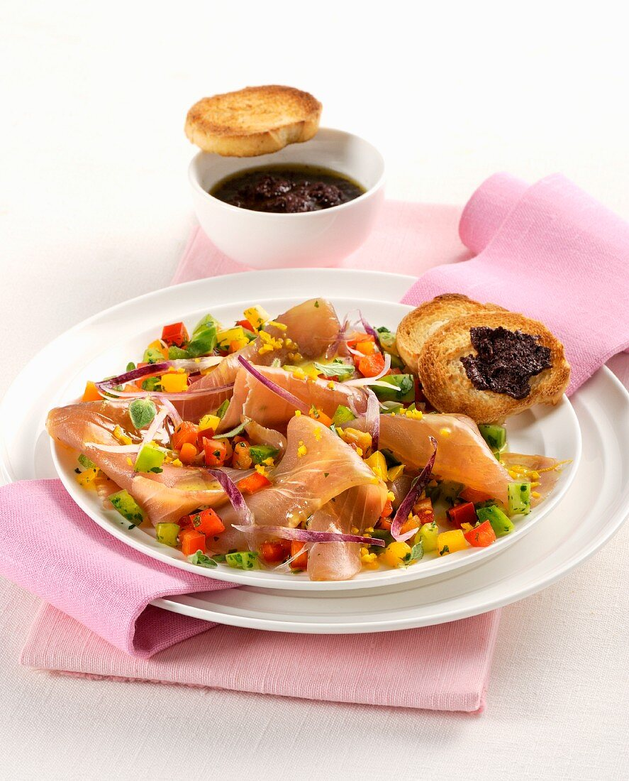 Smoked tuna fish with spring onions and peppers served with crostini with olive cream