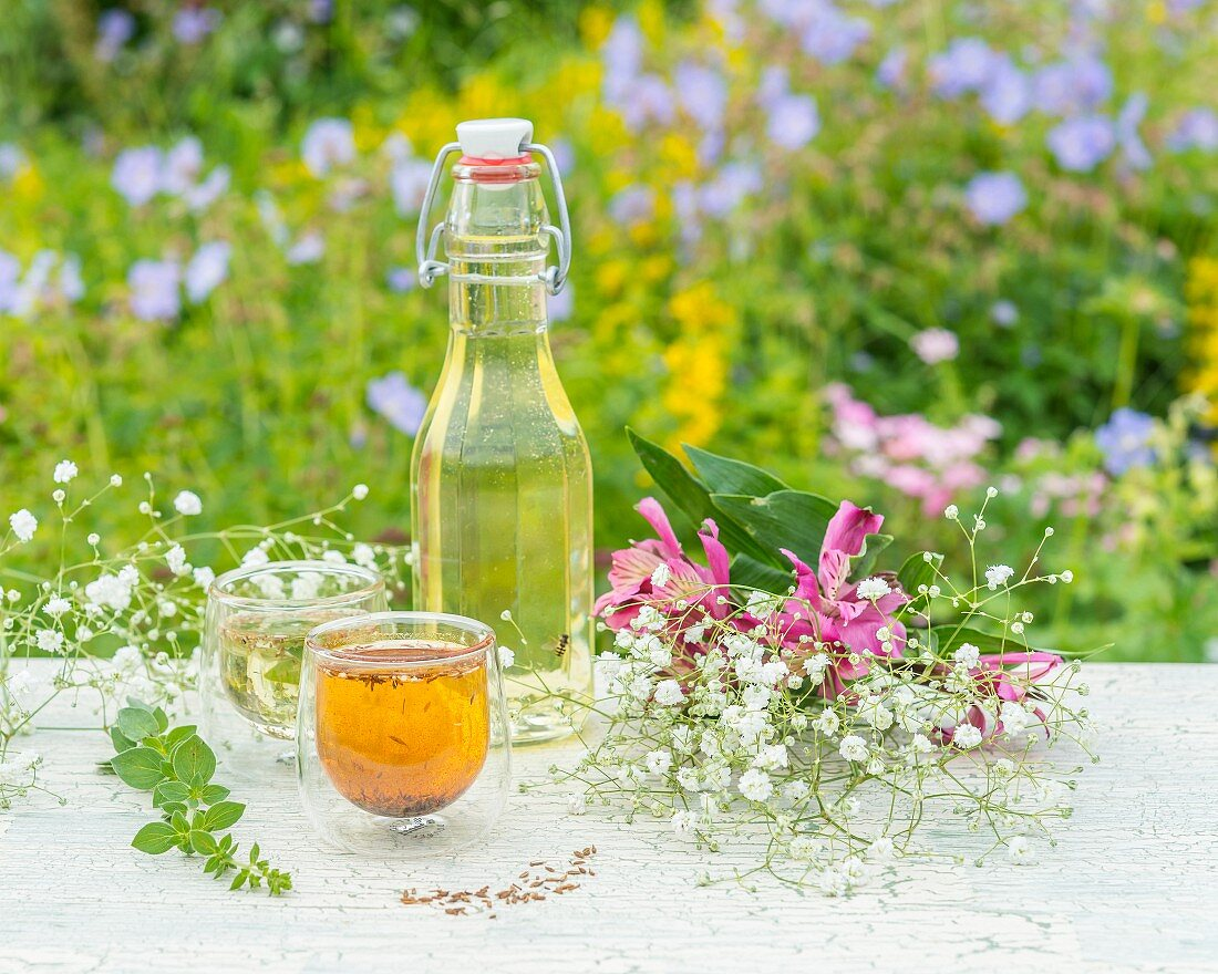 Homemade herb oil and flowers on a garden table