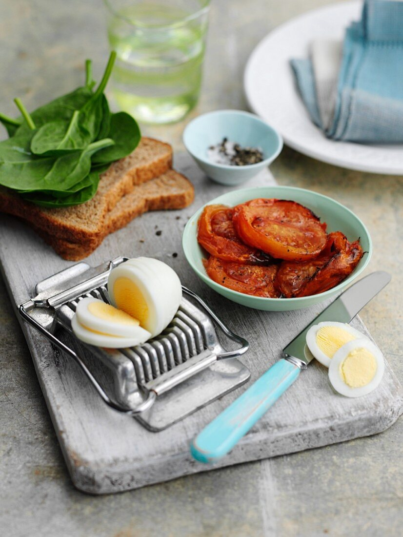 Ingredients for a sandwich with roasted tomatoes, spinach and a hard-boiled egg