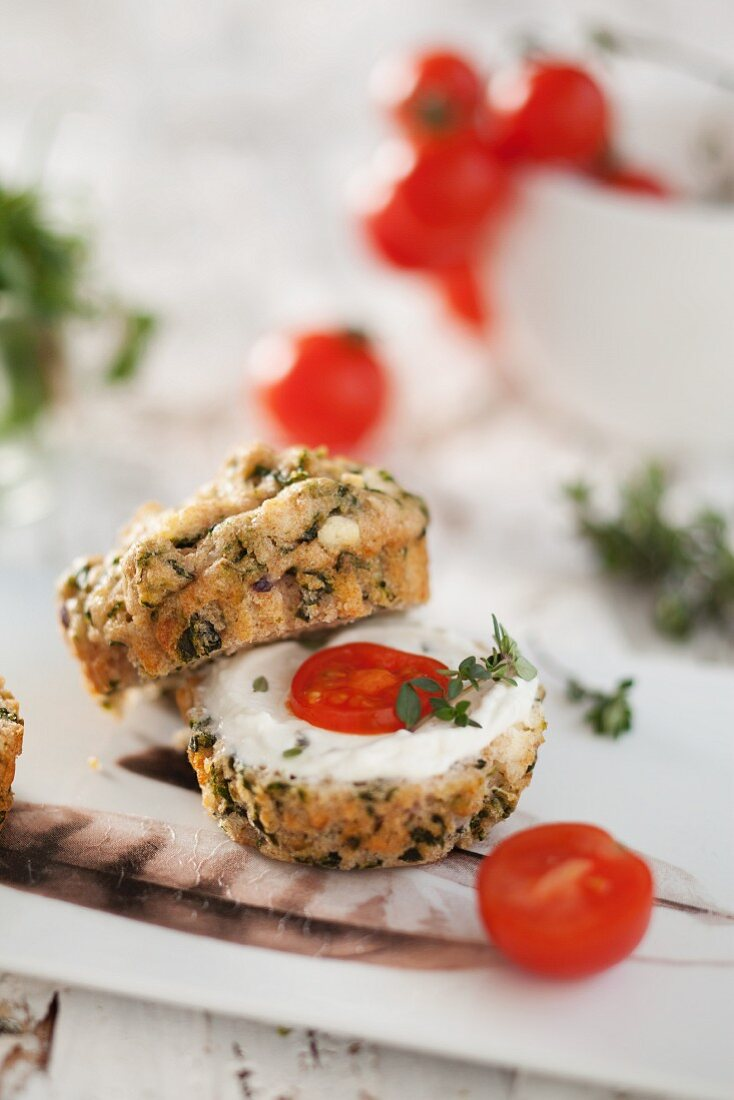 A spinach muffin, cut in half and topped with cream cheese and tomatoes