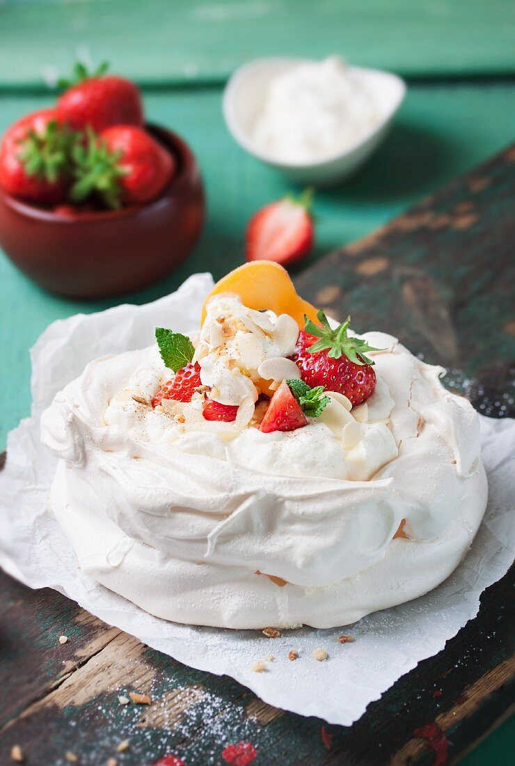 Pavlova with whipped cream, fruit and almonds