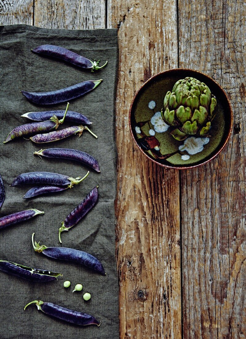 Purple pea pods and an artichoke