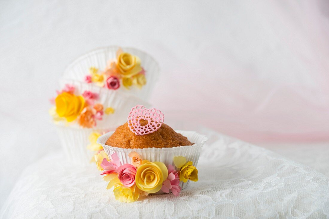 A cupcake in a paper case decorated with a sugar heart and paper flowers