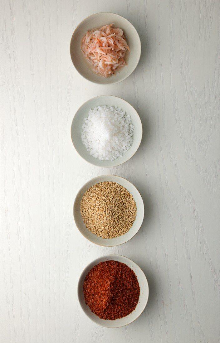 Salted shrimps, sea salt, sesame seeds and chilli powder in bowls