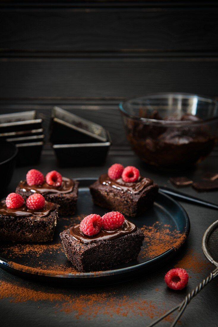 Kleine Schokoladenkuchen mit Himbeeren und Kakaopulver
