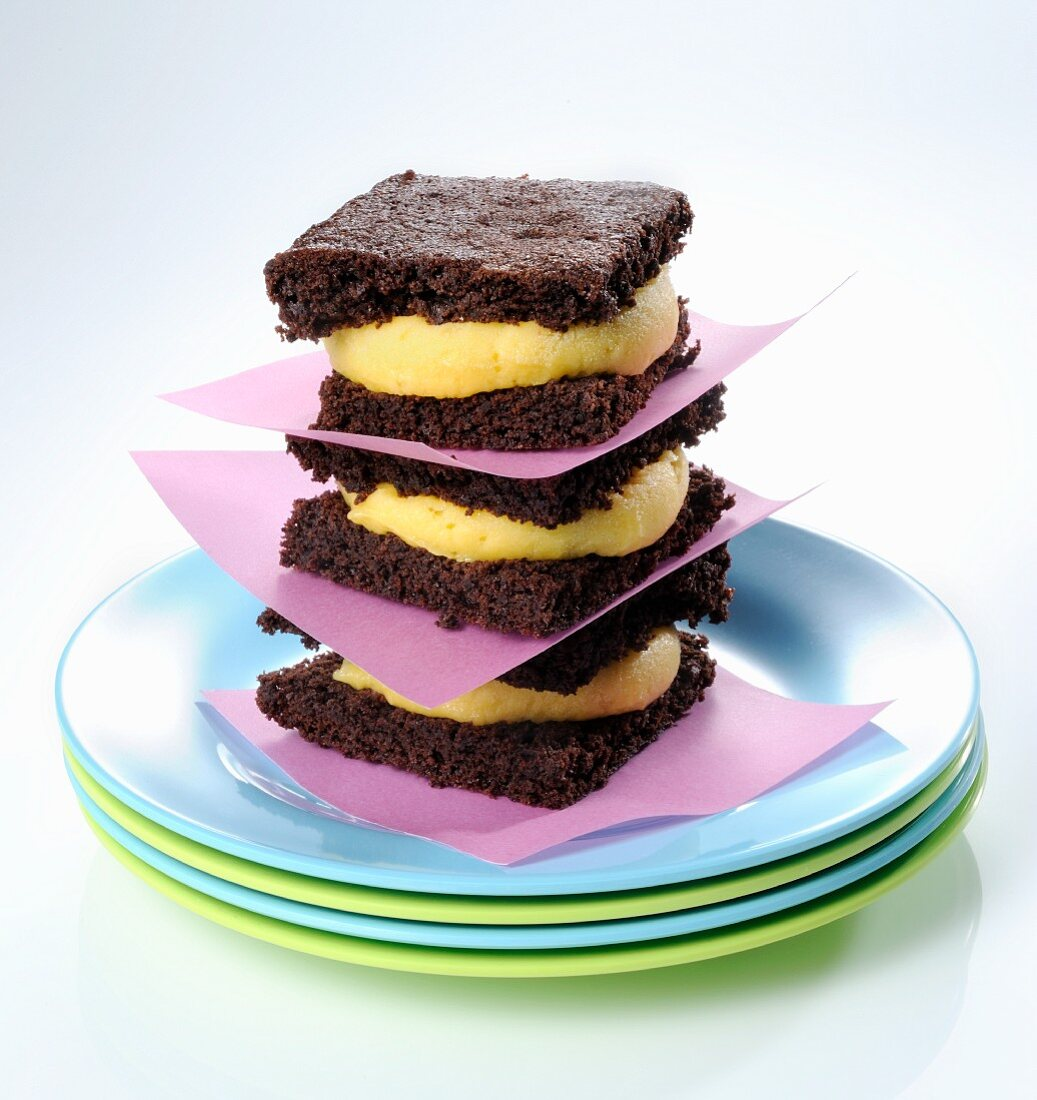 A stack of brownie sandwiches with mango cream