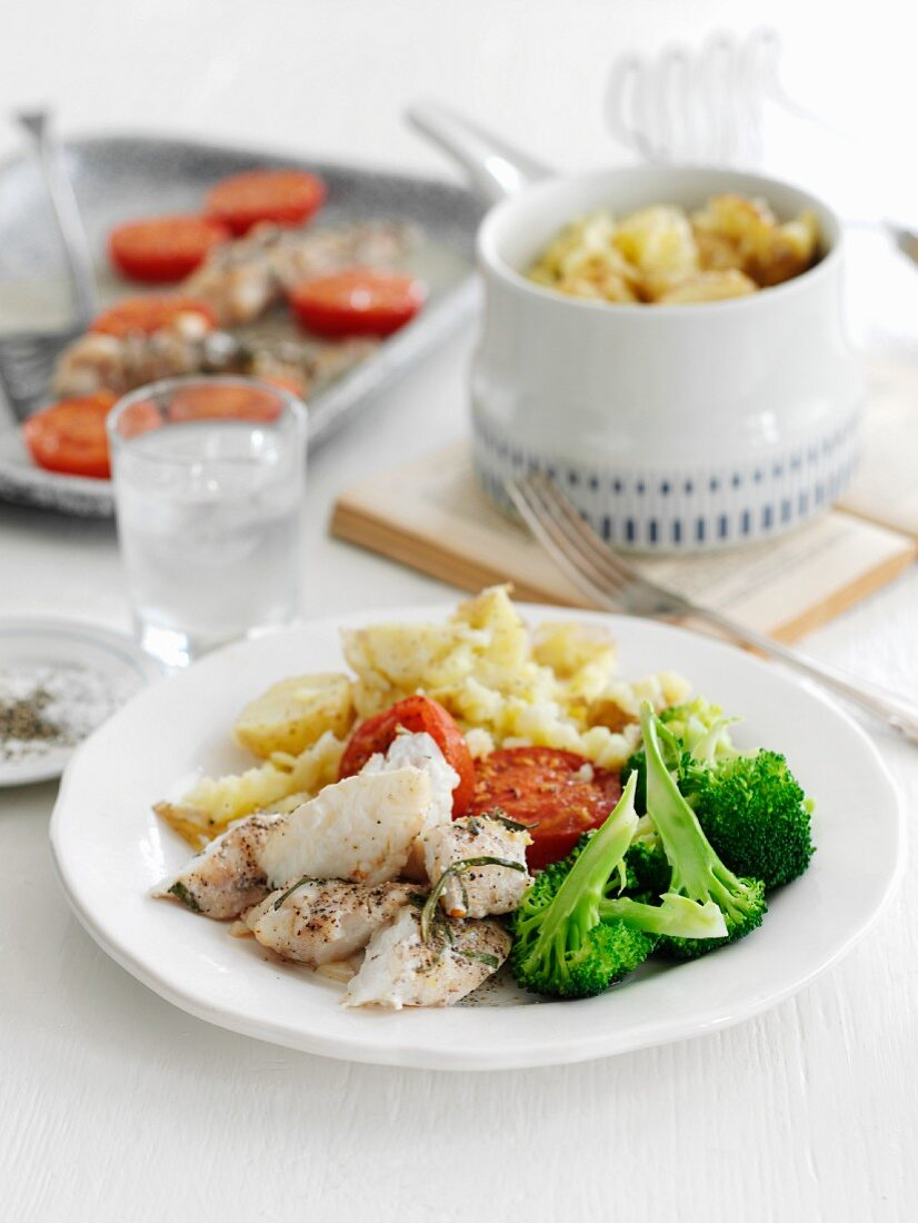 Baked monkfish with rosemary, potatoes, broccoli and tomatoes