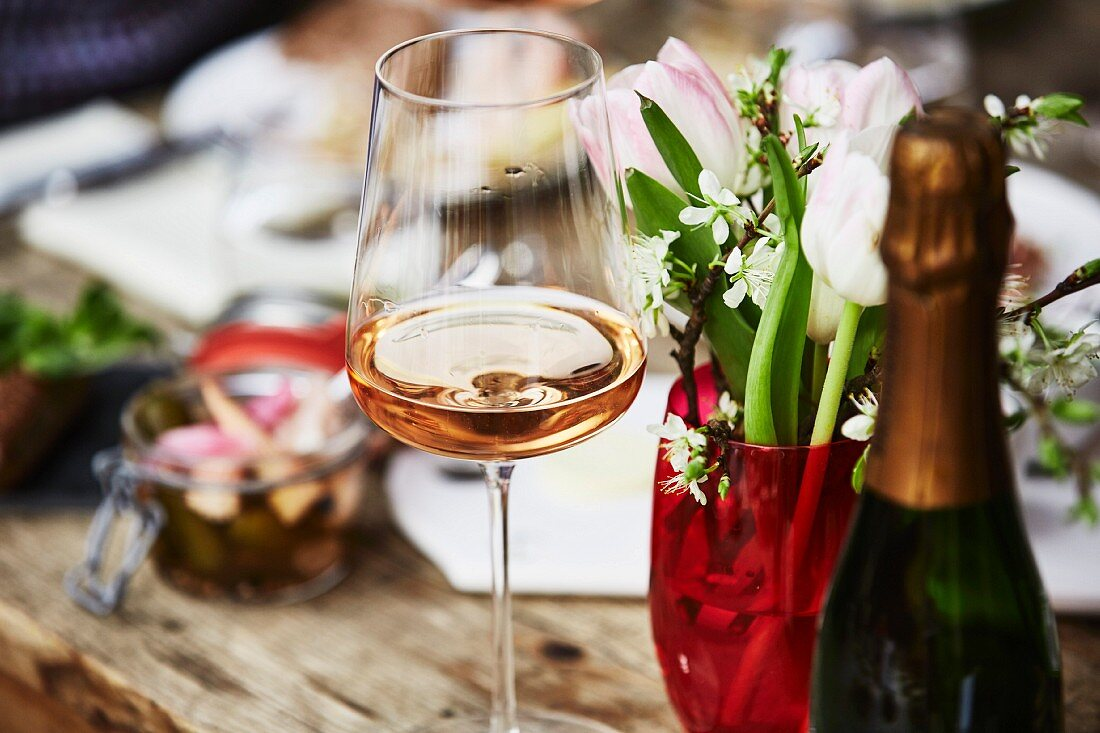 A glass of rosé champagne, a bunch of spring flowers and a bottle of champagne on a wooden table