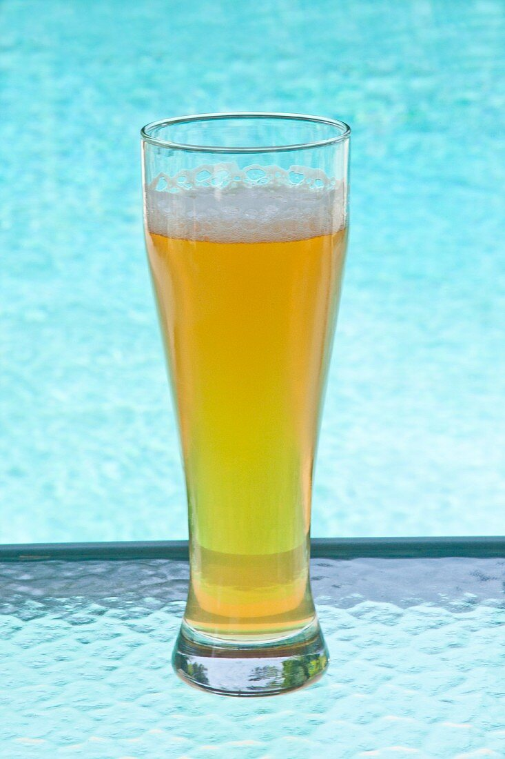 A glass of cold beer by a swimming pool