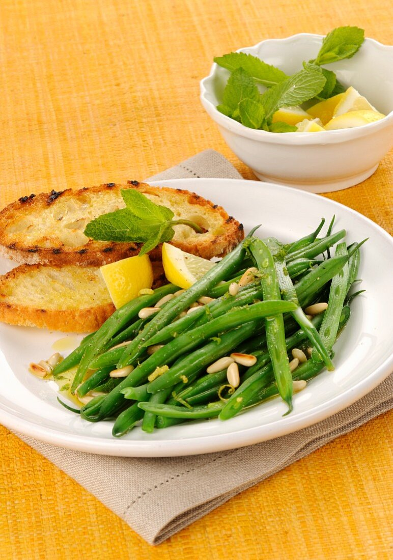 Steamed green beans with pine nuts and lemon juice served with grilled bread with olive oil