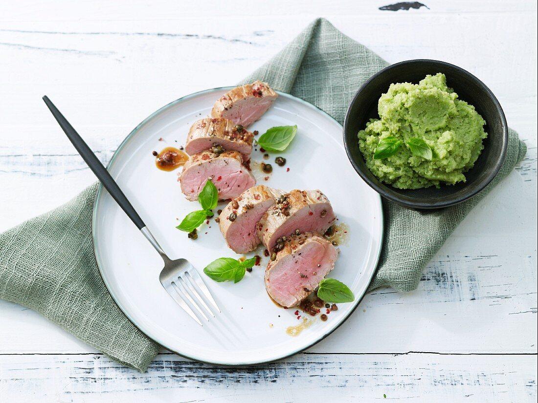 Peppered pork fillet cooking aluminium foil with Romanesco broccoli purée