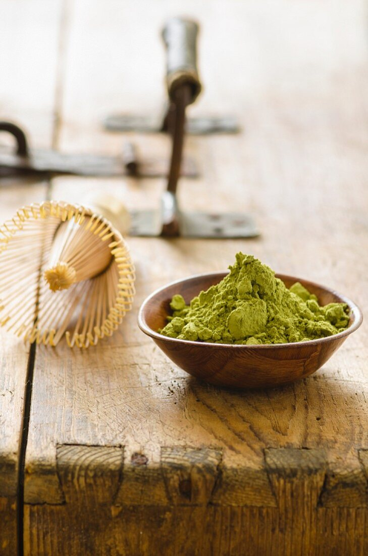 An arrangement of matcha powder and a tea whisk on a wooden table