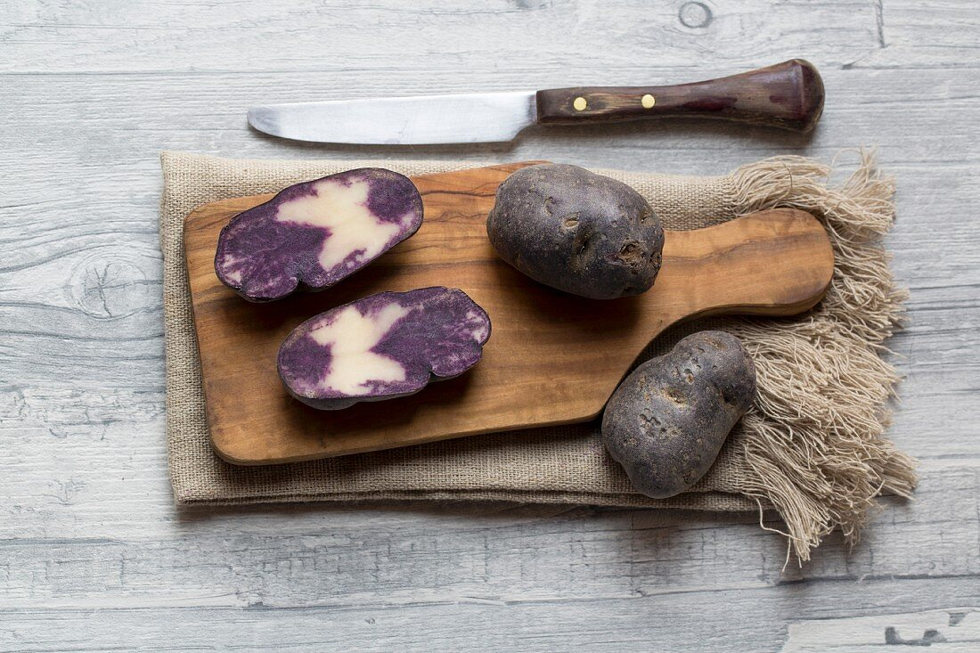 Purple potatoes, whole and halved on a wooden chopping board