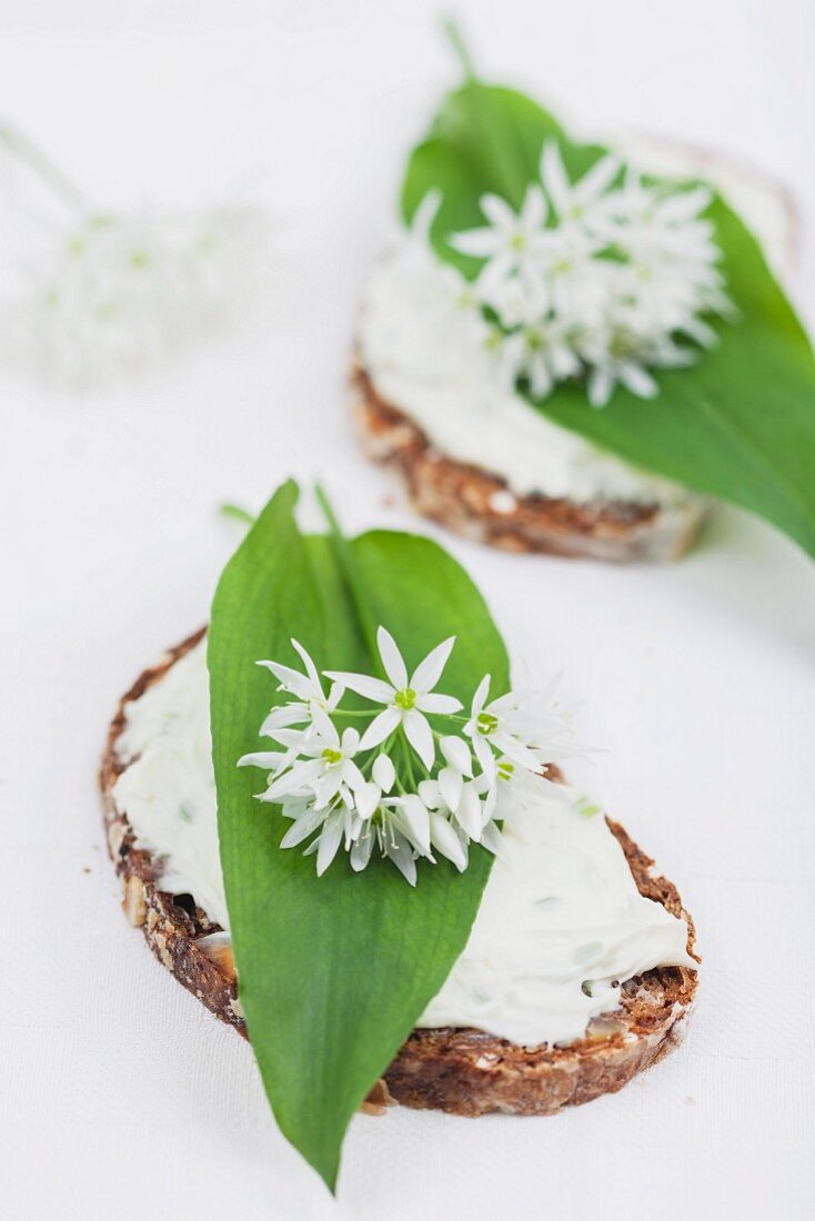Slices of bread topped with cream cheese, wild garlic leaves and edible wild garlic flowers