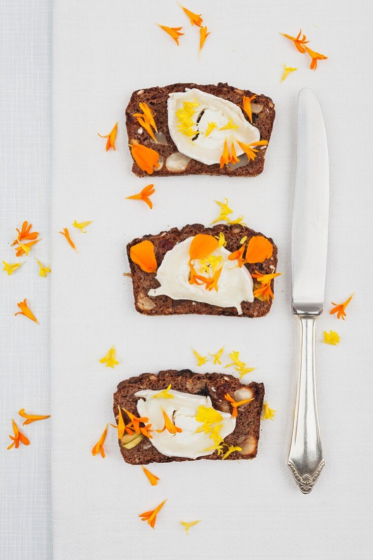 Three slices of homemade ginger bread with cream cheese and marigold petals