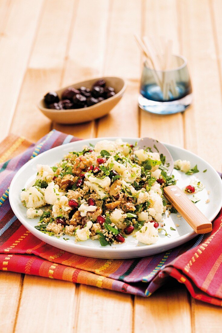 Couscous salad with cauliflower, pomegranate seeds and walnuts